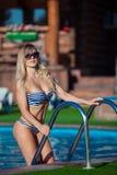 Schöne junge Frau in einem hübschen Badeanzug steht auf Treppe im Swimmingpool Sie lächelt so wunderbar Stockfotos