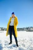 Schöne junge Frau in einem helles Gelb unten-aufgefüllten Mantel wirft für die Kamera auf Lizenzfreies Stockbild