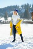 Schöne junge Frau in einem helles Gelb unten-aufgefüllten Mantel wirft für die Kamera auf Stockbilder