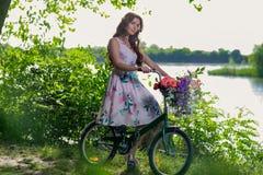 Schöne junge Frau in einem Kleid und in einem Hut auf einem Fahrrad auf dem nationalen Stockbild