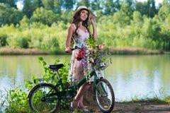 Schöne junge Frau in einem Kleid und in einem Hut auf einem Fahrrad auf dem nationalen Stockfoto