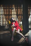 Schöne junge Frau in einem korallenroten Mantel und in den Turnschuhen sitzt an stockbilder