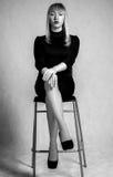Schöne junge Frau in einem kurzen Kleid, das auf dem Hochstuhl sitzt