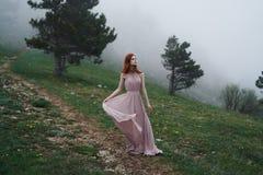 Schöne junge Frau in einem langen Kleid in den Bergen durch den Wald Stockbild