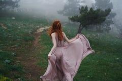 Schöne junge Frau in einem langen Kleid in den Bergen durch den Wald Stockbilder