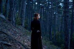 Schöne junge Frau in einem langen Kleid in einem dunklen Wald Stockfotos