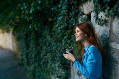 Schöne junge Frau in einem langen Kleid gehend um die Stadt mit einer Kamera Lizenzfreies Stockbild