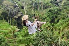 Schöne junge Frau an einem Pool Glückliche junge Frau im weißen Kleid und im Hut, die an der Palmenwaldung schwingt lizenzfreie stockfotos