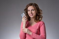 Schöne junge Frau in einem rosa Hemd drückt Gefühle mit s aus Stockbild