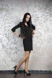 Schöne junge Frau in einem schwarzen Kleid auf abstraktem grauem Hintergrund Lizenzfreie Stockfotos
