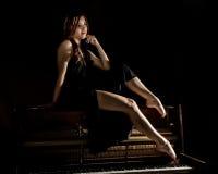 Schöne junge Frau in einem schwarzen Kleid mit einem offenen Rücken, der auf einem alten Klavier auf einem dunklen Hintergrund si Stockfotos