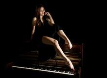 Schöne junge Frau in einem schwarzen Kleid mit einem offenen Rücken, der auf einem alten Klavier auf einem dunklen Hintergrund si Lizenzfreie Stockfotos