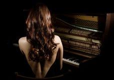 Schöne junge Frau in einem schwarzen Kleid mit sitzendem nere eines offenen Rückens das Klavier auf einem dunklen Hintergrund Stockfotos
