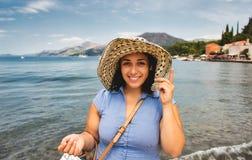 Schöne junge Frau in einem Strohhut auf dem Strand lächelnd an der Kamera lizenzfreies stockbild