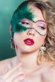 Schöne junge Frau in einer grünen mysteriösen venetianischen Maske ein Karneval des neuen Jahres, Weihnachtsmaskerade, ein Tanzcl Stockbild