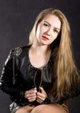 Schöne junge Frau in einer Lederjacke, die auf einem grauen Hintergrund aufwirft
