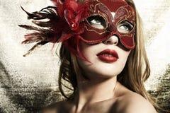 Schöne junge Frau in einer roten geheimnisvollen Schablone Stockfotografie