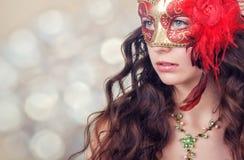 Schöne junge Frau in einer roten Karnevalsmaske Lizenzfreies Stockbild
