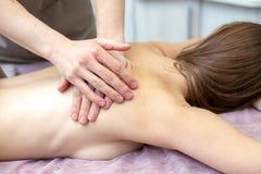 Schöne junge Frau empfängt eine Massage an einem Massagesalon lizenzfreies stockfoto