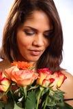 Schöne junge Frau empfängt rosafarbene Blumen Stockfoto