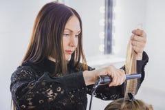 Schöne junge Frau erhält ihr Haar gerade gerichtet am Schönheitssaal stockbilder