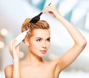 Schöne junge Frau färbt ihr Haar Stockfotografie