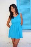 Schöne junge Frau gegen weißes Griechenland-Haus mit blauem Fenster Stockfotografie