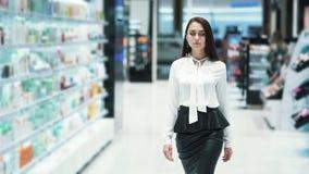 Schöne junge Frau geht durch Verkaufsbereich in den Kosmetik kaufen, Zeitlupe stock footage