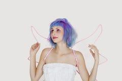 Schöne junge Frau gekleidet als Engel mit dem gefärbten Haar, das oben gegen grauen Hintergrund schaut Stockfotografie