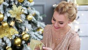 Schöne junge Frau hält eine Geschenkbox in den Händen nahe Weihnachtsbaum stock footage