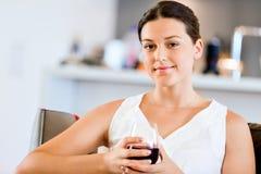 Schöne junge Frau halten Glas mit Rotwein Stockfotos