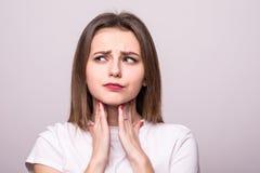 Schöne junge Frau hat Halsschmerzen, die Nahaufnahme, lokalisiert auf einem grauen Hintergrund lizenzfreie stockfotos