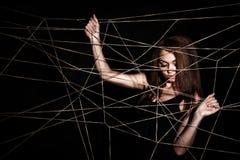 Schöne junge Frau hinter dem Netz von Seilen lizenzfreie stockbilder