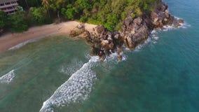 Schöne junge Frau im Bikini, der auf dem Steinufer steht Weg HD Slowmotion Video der Luftfliegen- Phuket, Thailand stock video footage