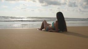 Schöne junge Frau im Bikini, der auf goldenem Sand auf Seestrand liegt und während der Sommerurlaubsreise sich entspannt gebräunt lizenzfreie stockfotos