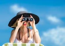 Schöne junge Frau im Bikini, der durch Ferngläser schaut Stockfoto