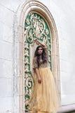 Schöne junge Frau im Goldkleid Stockbilder
