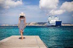 Schöne junge Frau im Hut gehend auf hölzernen Pier auf Sardinien stockbilder