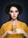 Schöne junge Frau im Hut und in der gelben Bluse mit Schale coffe Stockfoto