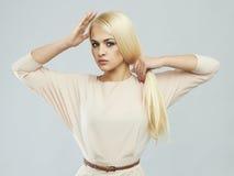 Schöne junge Frau im Kleid blondes Mädchenmodell mit dem starken gesunden Haar Stockfotos