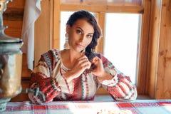Schöne junge Frau im nationalen Kostüm, das in einer Hütte sitzt lizenzfreie stockfotos