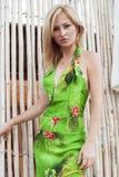 Schöne junge Frau im netten grünen Kleid, das auf weißer Bambuswand aufwirft Arbeiten Sie Foto, nettes blondes Haar, Sonnenbräune Lizenzfreies Stockfoto