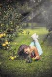 Schöne junge Frau im Overall im Apfelgarten Stockfotografie