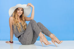 Schöne junge Frau im Overall, in weißem Sun-Hut und in den hohen Absätzen sitzt auf Boden Lizenzfreies Stockbild