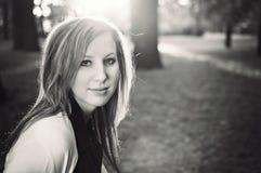 Schöne junge Frau im Park am Herbstsonnenuntergang lizenzfreies stockbild