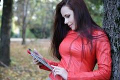 Schöne junge Frau im Park mit der Tablette Stockfoto