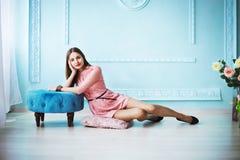 Schöne junge Frau im rosa Kleid, das auf dem Boden auf blauem Wandhintergrund sitzt stockfotografie