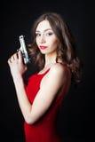 Schöne junge Frau im roten Kleid, das Gewehr hält Stockbilder