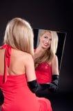 Schöne junge Frau im roten Kleid untersucht den Spiegel auf dunklem Hintergrund Stockbilder