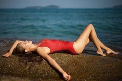 Schöne Frau im roten liegenden und ein Sonnenbad nehmenden Bikini Lizenzfreie Stockbilder